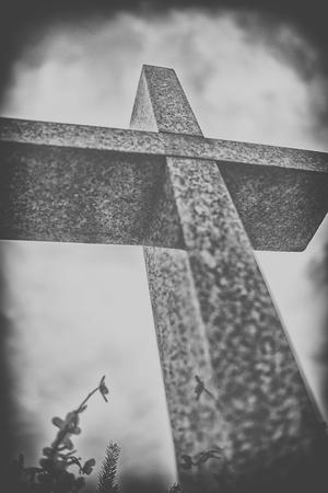 arrepentimiento: cruz de piedra contra el cielo nublado dramático, blanco y negro
