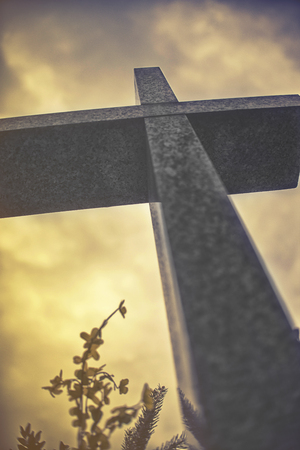 repentance: stone cross against dramatic cloudy sky, vintage effect