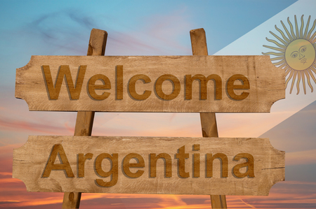 Welcome to  Argentina sing on wood background with blending national flag