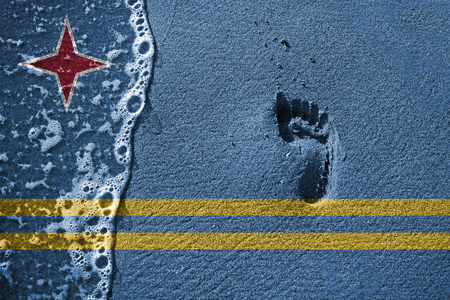 aruba flag: Sand, foot print and wave sea background or texture with blending  Aruba flag Stock Photo