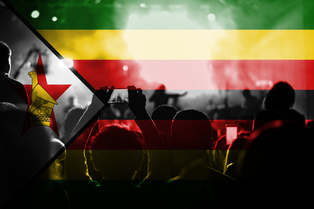 zimbabwe: live music concert with blending Zimbabwe flag on fans Foto de archivo