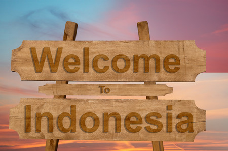 Welcome to Indonesia sing on wood background with blending national flag