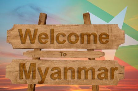 Welcome to Myanmar sign on wood background with blending national flag