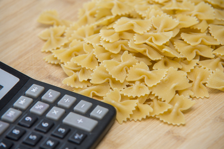 calulator with pasta on wooden background, calories Stock Photo