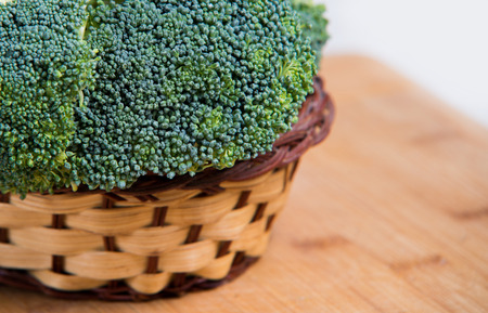 solated on white: close up on Fresh broccoli solated in basket on wood and white background Stock Photo