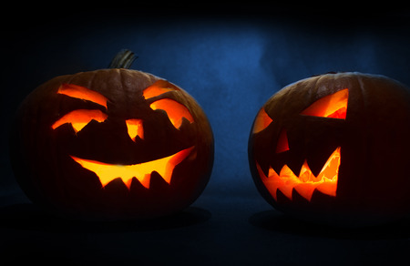 Two carved faces of pumpkins glowing on Halloween on blue background