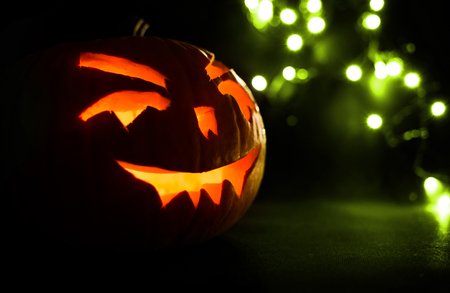 carved face of pumpkin glowing on Halloween on green bokeh light background