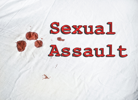 coward: Sexsual Assault sign on white sheet with blood Stock Photo