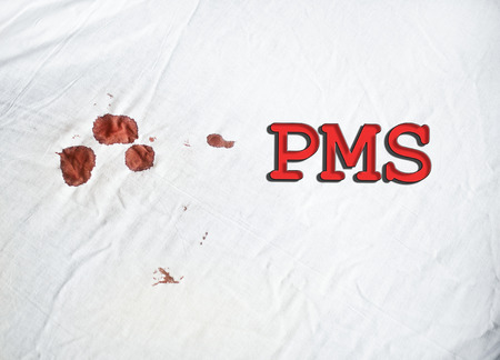 premenstrual syndrome: PMS sign on white sheet with blood Stock Photo