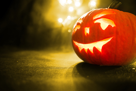 carved face of pumpkin glowing on Halloween on yellow bokeh light background Stock Photo