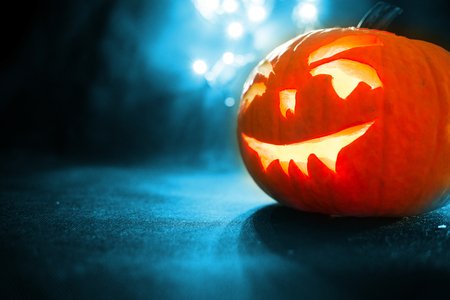 carved face of pumpkin glowing on Halloween on blue bokeh light background Stock Photo