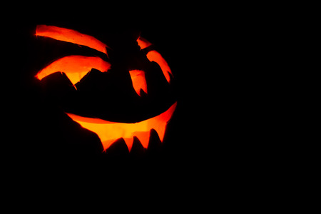 carved face of pumpkin glowing on Halloween black background