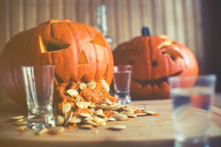 Pumpkin puking with pumpkin seeds on wood table, vodka, vintage effect Stock Photo