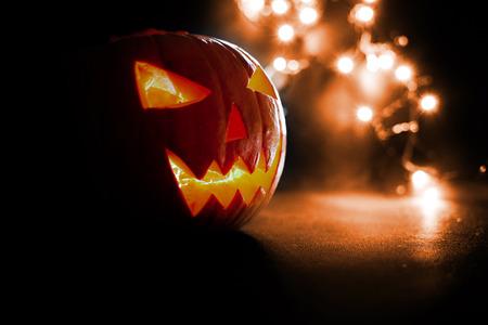 Scary Halloween pumpkins on a orange light background.