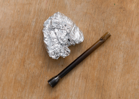 Marijuana in tin foil with pipe on wooden table