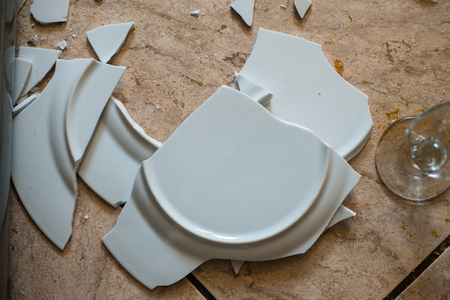 plates of food: close up on broken dishes on the floor