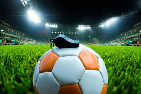 Voetbalbal met fluitje op het gras op voetbalstadion Stockfoto