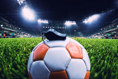 Voetbalbal met fluitje op het gras op voetbalstadion, uitstekend effect Stockfoto