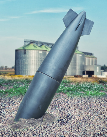 close up on misfire or unexploded  bomb with the factory on background Stock Photo