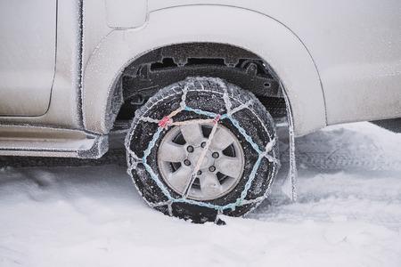 Auto Rad mit Schneeketten hautnah. Winter Hintergrund Standard-Bild - 94644312