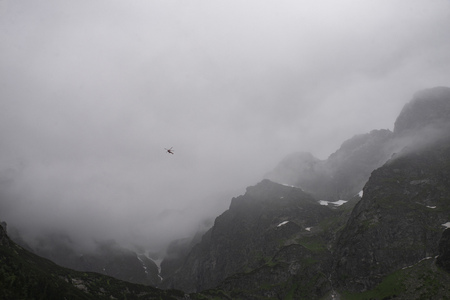 rescue helicopter in the mountains, heavy fog, Tatra 免版税图像