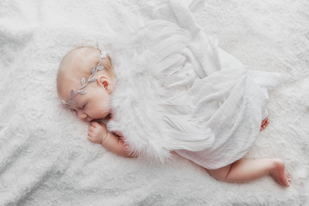 close up on newborn baby girl, angel wings, top view