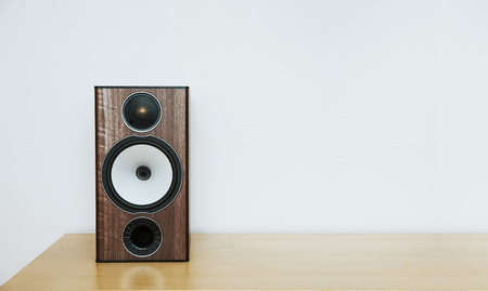speaker on a wooden table with copyspace, white background