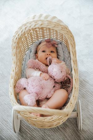 newborn in a toy wicker trolley, top view