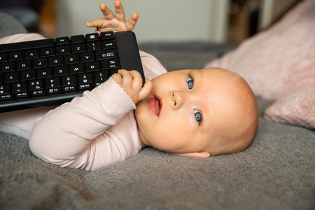 small child, first steps on the internet, a newborn baby is holding a keyboard from the computer