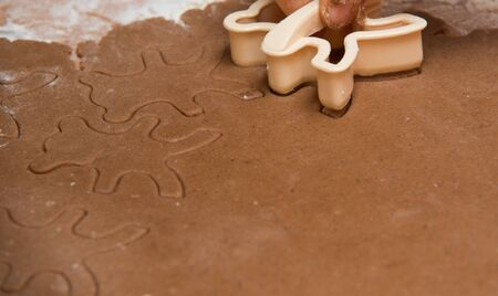 cutting out  a gingerbread with human hand