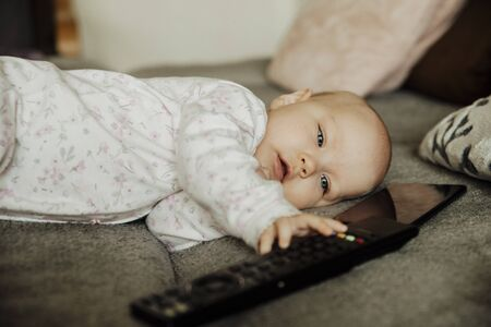 a child with a remote control and a telephone,c
