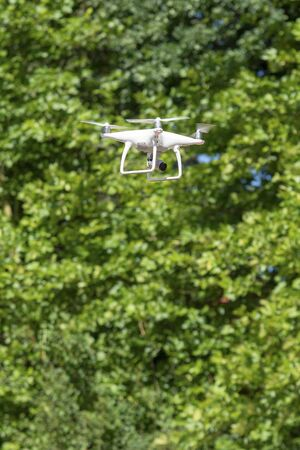 close up on drone in the air against green trees Stok Fotoğraf