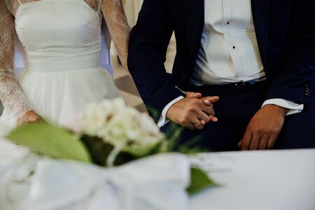 the young couple holds hands during the wedding Фото со стока