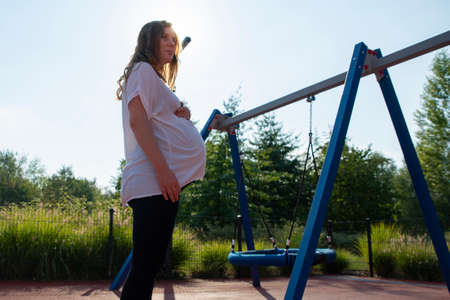 lonely pregnant woman on the playground Reklamní fotografie