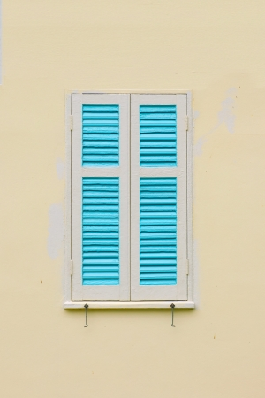 Window with shutters open or closed on wall photo