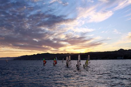 windsurfers: Windsurfers float in the sea against a decline Stock Photo