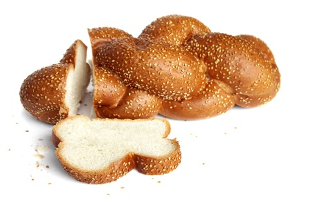 Cut braided white bread, sprinkled with sesame seeds on white background photo