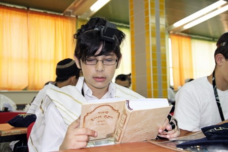 tefillin: Jewish Boy reads a prayer book in the school synagogue Stock Photo
