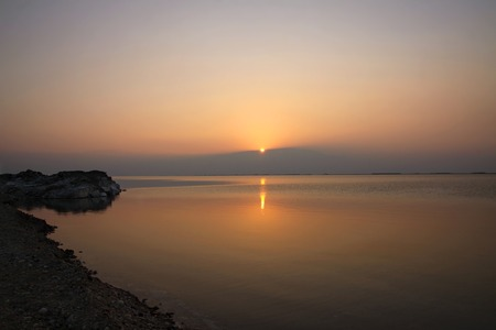 rising dead: Reflection in the water and the rising sun in the Dead Sea