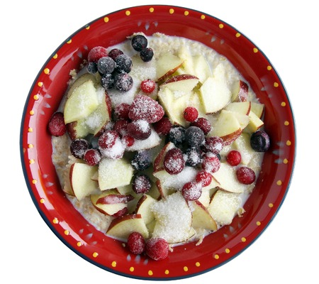 kasha: Ceramic plate with porridge, apple slices and berries isolated on white Stock Photo