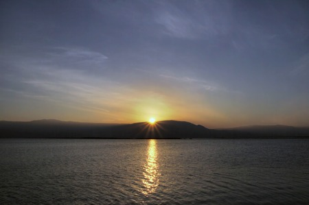 rising dead: Reflection in the water and the rising sun over the Dead Sea Stock Photo
