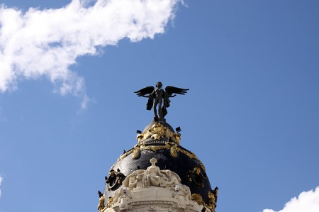 gran via: MADRID, SPAIN - OCTOBER 04, 2013: Sculpture of an angel on the roof of a historical building on the Gran Via in Madrid Editorial