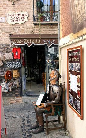 don quijote: TOLEDO, ESPA�A - 07 de octubre 2013: Escultura de Don Quijote sentado en una silla y la celebraci�n de un men� en la parte delantera del restaurante