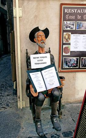 don quijote: TOLEDO, ESPAÑA - 07 de octubre, 2013: Escultura de Don Quijote, la celebración de un menú de un restaurante. La inscripción en español: No me toques estoy trabajando