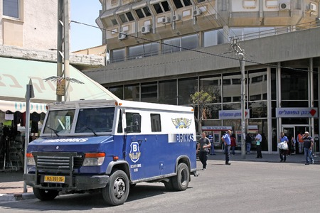 armored car: BEER SHEVA, ISRAEL - APRIL 04, 2014: Collection of cash from the bank by a Brinks armored car company Editorial
