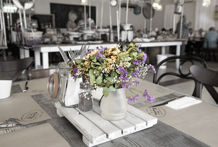 kibbutz: KIBBUTZ SNIR, ISRAEL - MAY 27, 2015: Table setting in a rustic style with a bouquet of  dry flowers