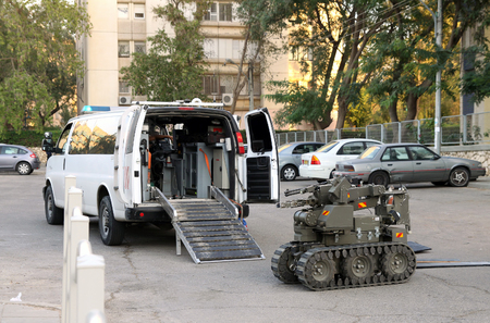 radio unit: BEER SHEVA, ISRAEL - NOVEMBER 18, 2012:  Military or police robot used to safely move or detonate bombs and mines enters a vehicle for transportation