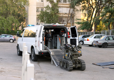 radio unit: BEER SHEVA, ISRAEL - NOVEMBER 18, 2012:  The police or military robot for working with bomb enters a vehicle for transportation