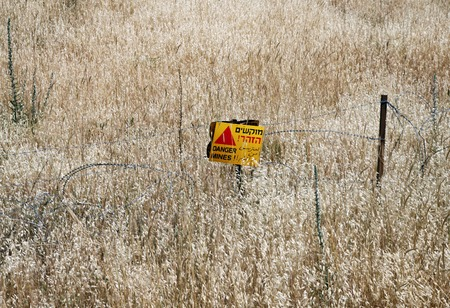 the golan heights: Minefields on the Golan Heights, Israel. Warning signs in three languages Stock Photo