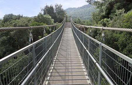 gully: Modern suspension bridge over the ravine Stock Photo